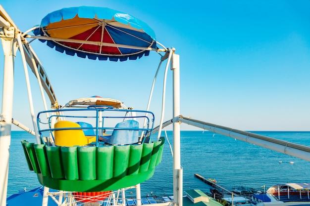 Roda gigante colorida do parque de diversões no céu azul