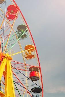 Roda gigante contra céu azul claro em parque de diversões