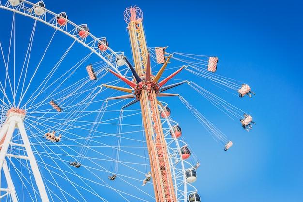 Roda-gigante e carrossel com correntes em um parque de diversões