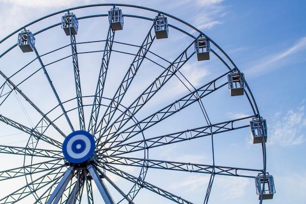 Roda gigante em um fundo de céu azul e nuvens brancas à noite