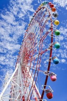 Roda gigante gigante colorida com céu azul e nuvens