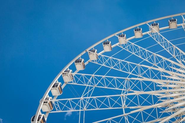 Roda-gigante grande branca com fundo de nuvens nítidas de céu azul