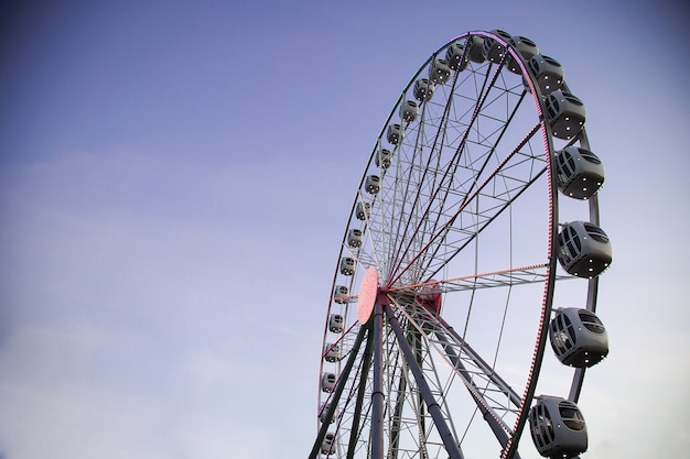 Roda gigante iluminada contra um céu escuro à noite. parque de diversões. atividades de lazer