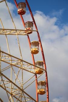 Roda-gigante moderna do close-up contra o céu azul e as nuvens brancas, festival do divertimento
