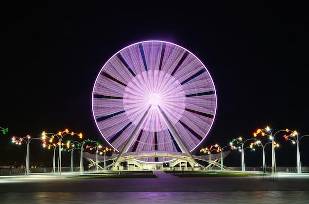 Roda-gigante na avenida em baku, perto do mar cáspio, filmada à noite em uma longa exposição, com efeitos de luz colorida.