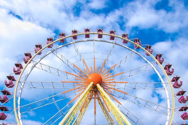 Roda gigante sobre o céu azul com nuvens brancas