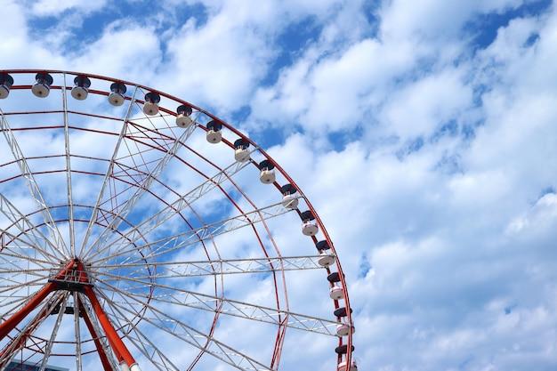 Roda gigante vermelha e branca contra o céu azul e nublado, com espaço de cópia