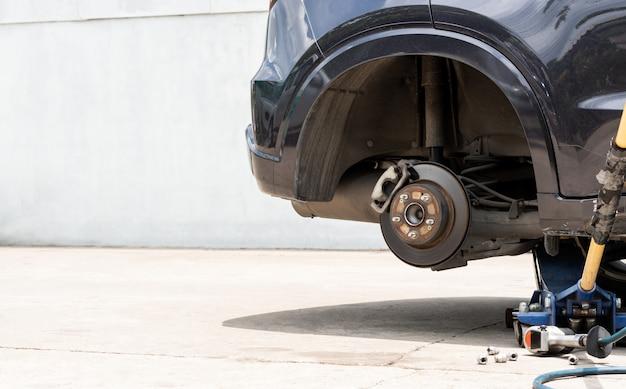 Roda nova ao ar livre do pneu que substitui, reparo do pneu de carro do acidente que repara o serviço usando o jaque e a chave de fenda elétrica
