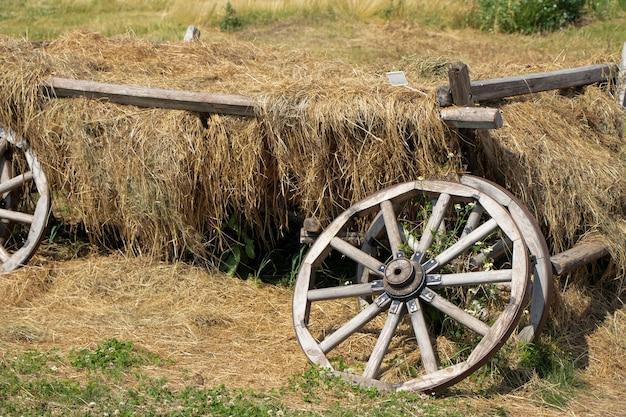 Roda quebrada de uma carroça com feno velha carroça agrícola desabou feno roda espalhada arrancada