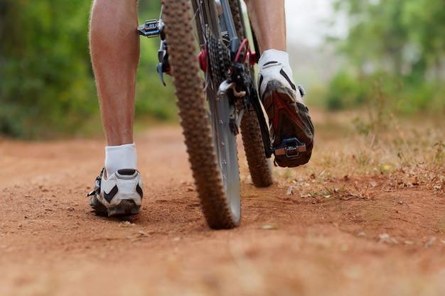 Roda traseira de bicicleta de montanha e pé de cavaleiros. tiro traseiro da bicicleta de montanha na estrada de terra marrom. feche acima da vista de um pneu de bicicleta de montanha.
