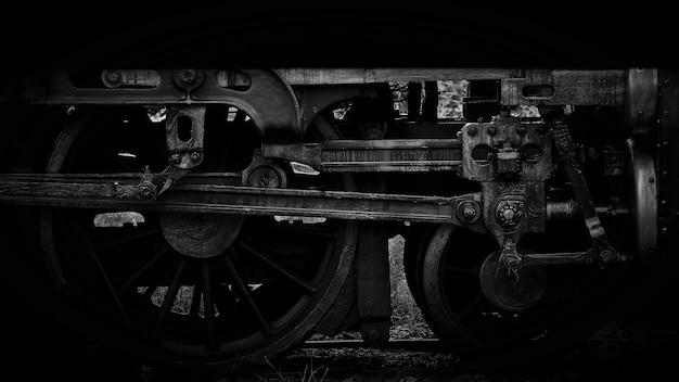 Roda velha de locomotiva a vapor e varas - monocromático
