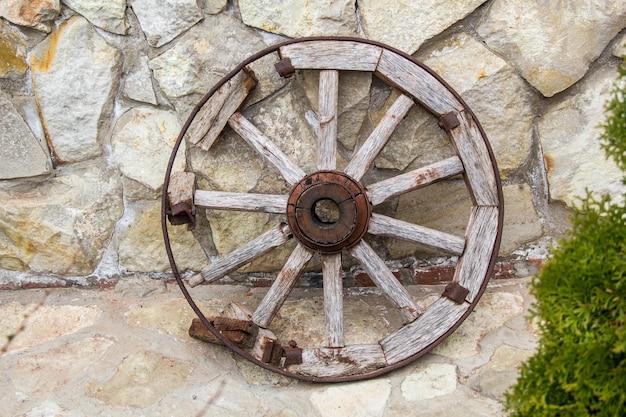 Roda velha de madeira e metal no fundo da parede de pedra