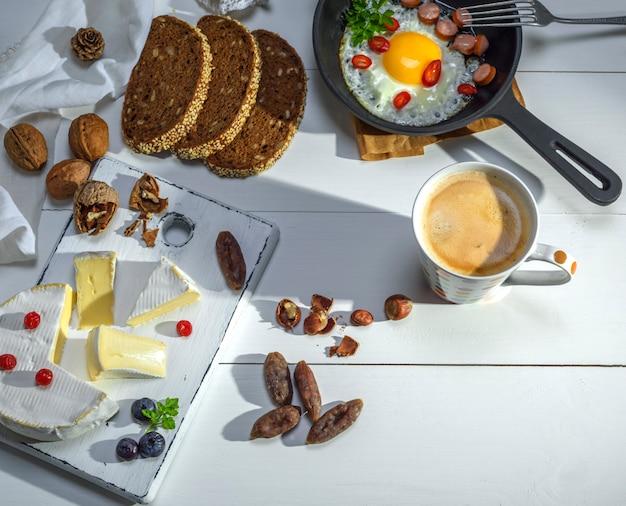 Rodada de queijo camembert em um quadro branco, ovos fritos com salsicha e uma xícara de café