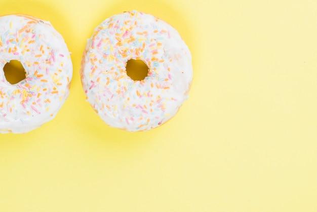 Rodada donuts de geada em fundo amarelo