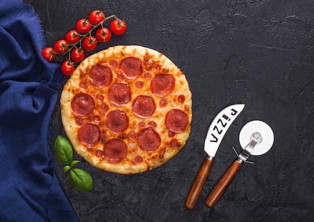 Rodada fresca assada pizza italiana de pepperoni com cortador de roda e faca com tomate e manjericão no fundo preto da mesa da cozinha.