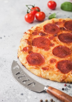Rodada fresca assada pizza italiana de pepperoni com faca com tomate e manjericão no fundo da mesa da cozinha.