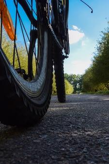 Rodas de bicicleta andando em uma estrada de asfalto contra um fundo de céu azul brilhante
