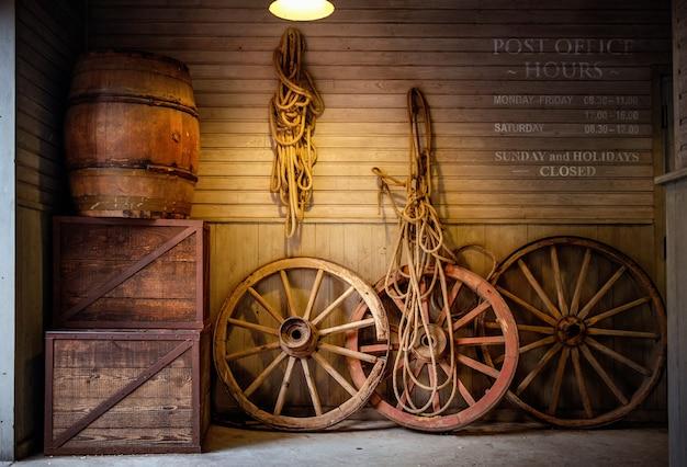 Rodas de carrinhos antigos, caixas e barris de vinho.