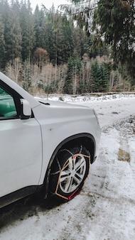 Rodas de carros acorrentadas fecham o espaço da cópia da estrada coberta de neve