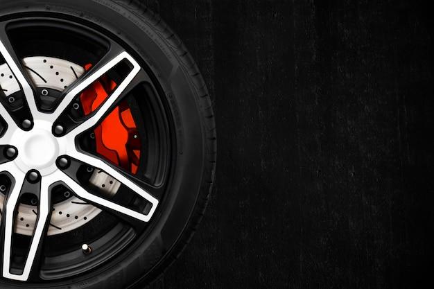 Rodas de liga de carro de corrida com discos de freio de metal e pinça vermelha em uma parede de cimento preto