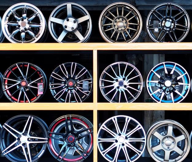 Rodas novas da liga na loja moderna do pneu com suporte.