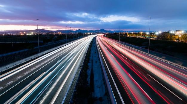 Rodovia ao pôr do sol com veículos dirigindo em duas direções, deixando trilhas de luz