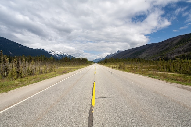 Rodovia cercada por uma paisagem montanhosa sob o céu nublado no canadá