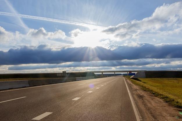 Rodovia e viaduto sob as nuvens azuis e sol brilhante.