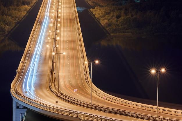 Rodovia nas luzes da noite. caminho rápido da luz do carro, trilhas e faixas na estrada da ponte de intercâmbio. listras pintadas à luz noturna