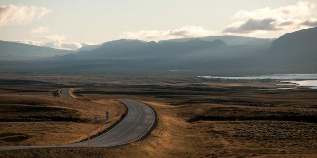Rodovia pavimentada que meandra através da terra seca para montanhas enevoadas