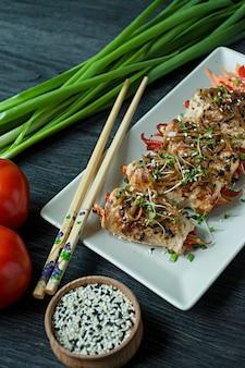 Rola com peito de frango fresco com verdes, fatias de cenoura, pimentão em uma placa de corte escura.