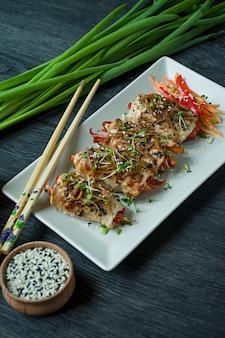 Rola com peito de frango fresco com verdes, fatias de cenoura, pimentão em uma placa de corte escuro.