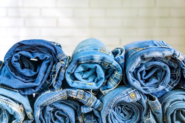 Role as calças de brim azuis dispostas na pilha na parede. conceito de roupas de moda e beleza