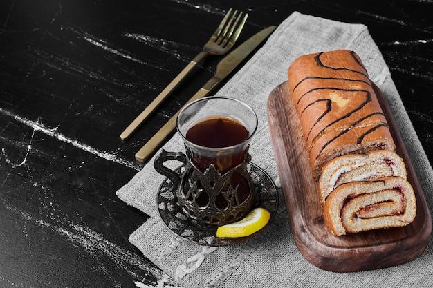Role as fatias de bolo com um copo de chá.