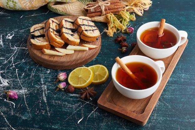 Role as fatias de bolo com uma xícara de chá de ervas.