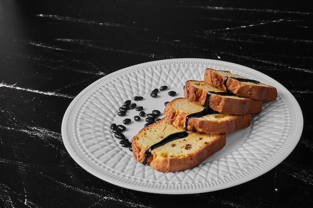 Role as fatias de bolo em um prato branco.