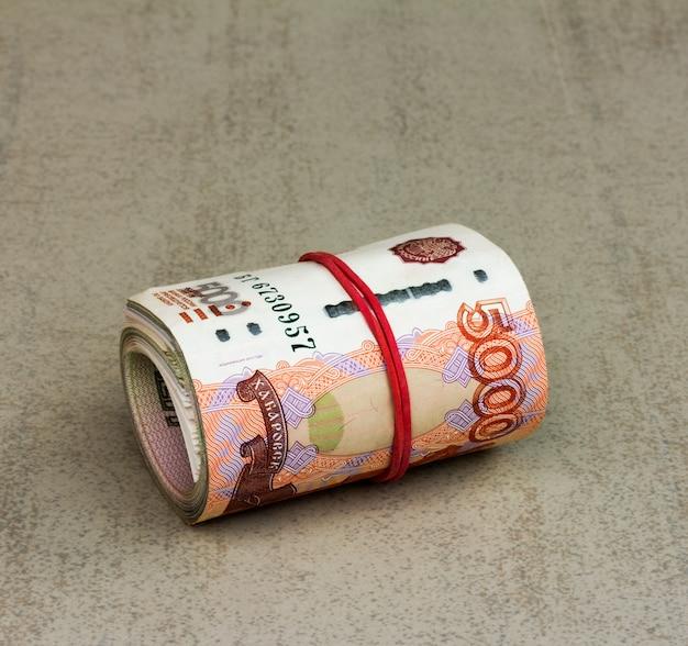 Role as notas russas sobre um fundo cinza closeup