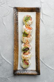 Role com salmão e microgreen no prato de cerâmica
