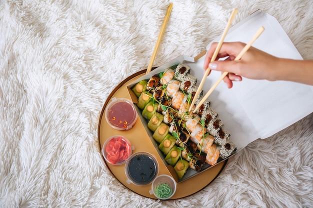 Role na mão da menina no contexto de uma bandeja com sushi.