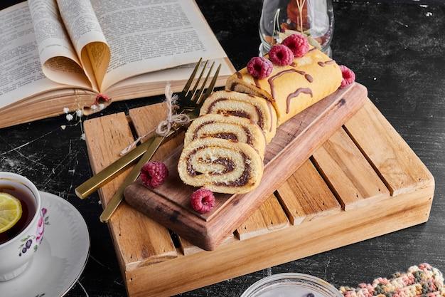 Role o bolo com creme de chocolate e uma xícara de chá em uma bandeja de madeira.