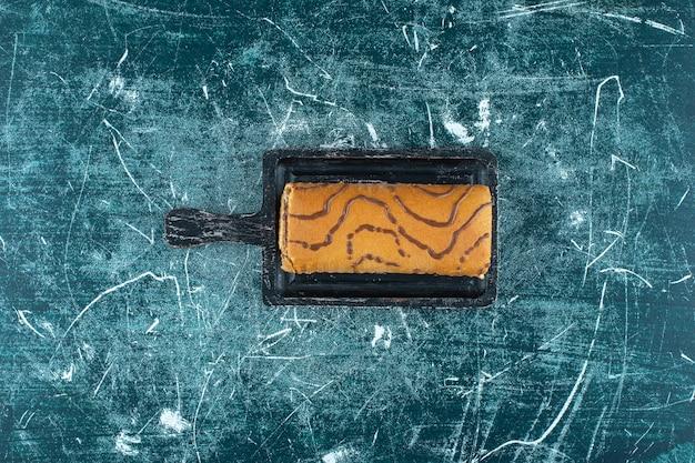 Role o bolo em uma placa, sobre o fundo azul. foto de alta qualidade