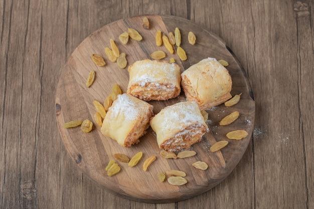 Role os biscoitos com passas e recheios sobre uma placa de madeira.