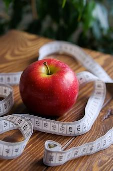 Roleta e uma maçã vermelha em uma mesa de madeira. o conceito de dieta, nutrição saudável.