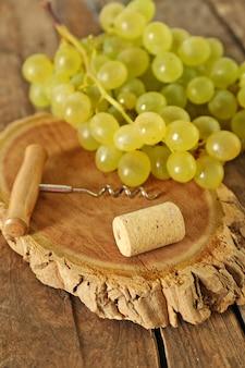 Rolha de vinho e tailspin com cacho de uvas na superfície de madeira
