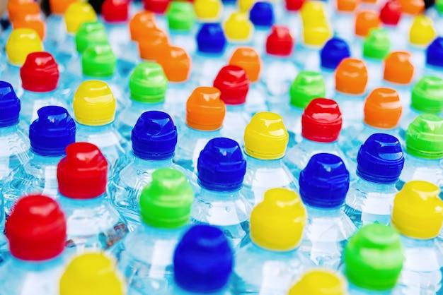 Rolhas coloridas de garrafas plásticas novas, conceito da poluição por plásticos recicláveis.