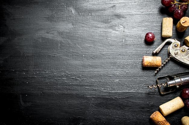 Rolhas de vinho com saca-rolhas e ramo de uva na mesa de madeira preta.