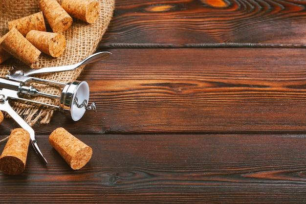 Rolhas de vinho com saca-rolhas na mesa de madeira
