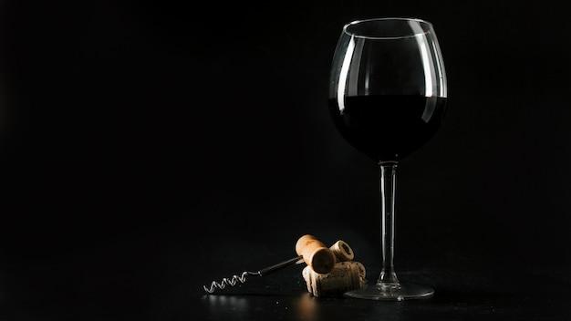 Rolhas e saca-rolhas perto de um copo de vinho