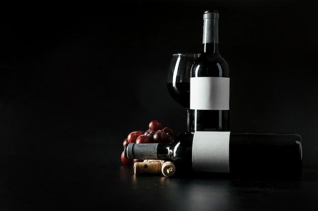 Rolhas e uvas perto de garrafas e copos de vinho