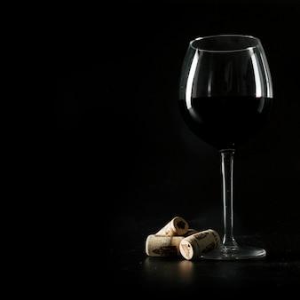 Rolhas perto de um copo de vinho